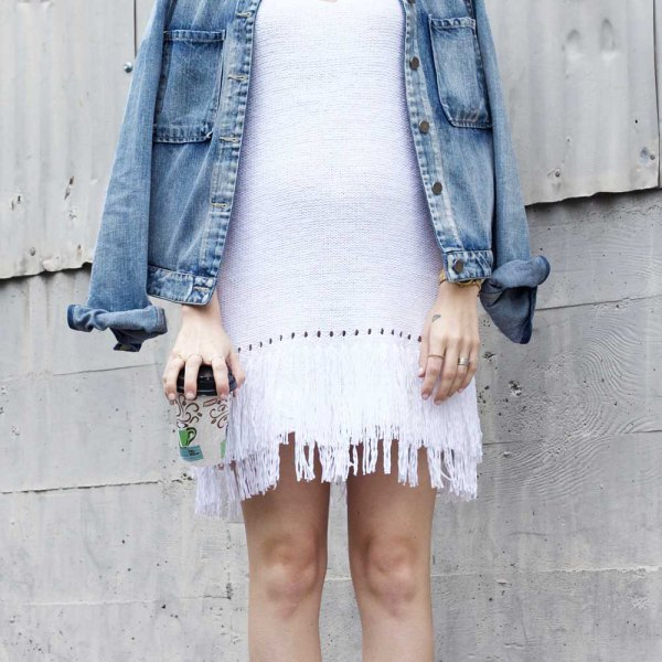 white shift dress denim jacket draped over shoulders