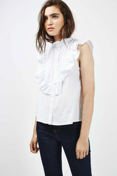 sleeveless white ruffle blouse dark blue skinny jeans