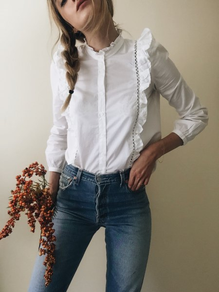 white ruffle form fitting blouse blue skinny jeans