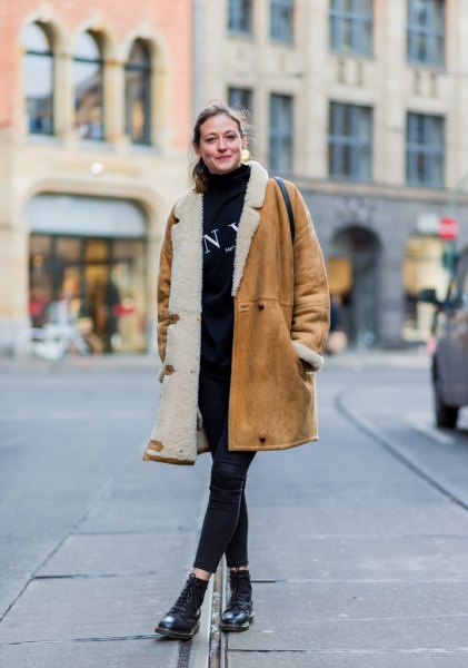 brown long shearling coat with black sweater and cropped jeans