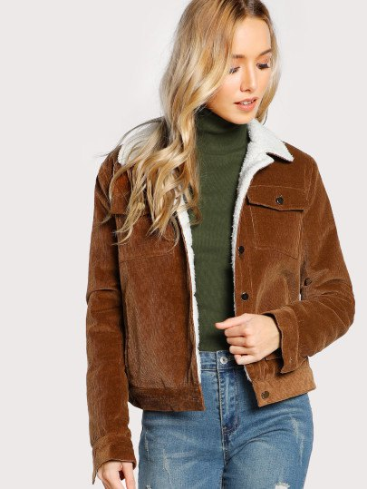 brown sherpa lined jacket with green turtleneck sweater and jeans
