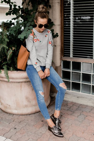 grey embroidered sweatshirt with blue ripped skinny jeans