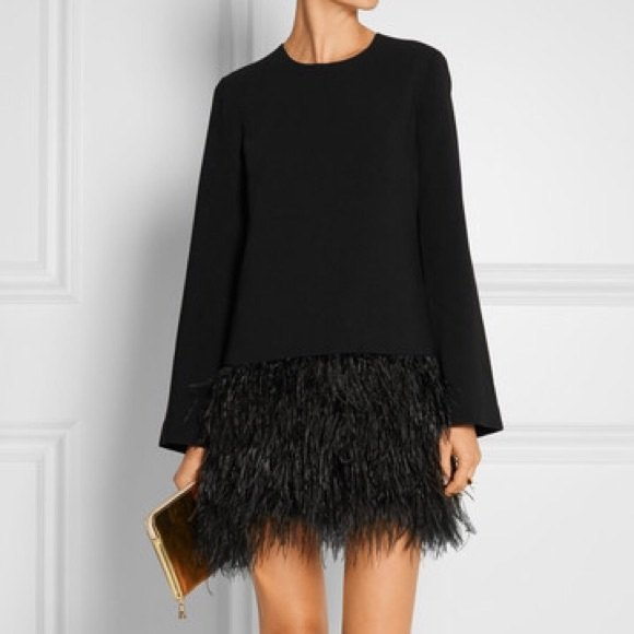 two toned black long sleeve feather dress with gold clutch bag