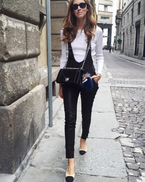 white mock neck fitted sweater with black leather overalls