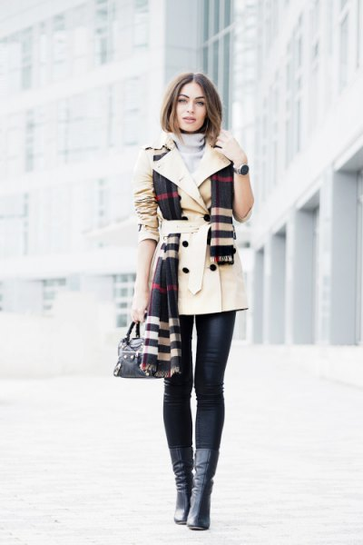 beige belted trench coat with black and white plaid scarf