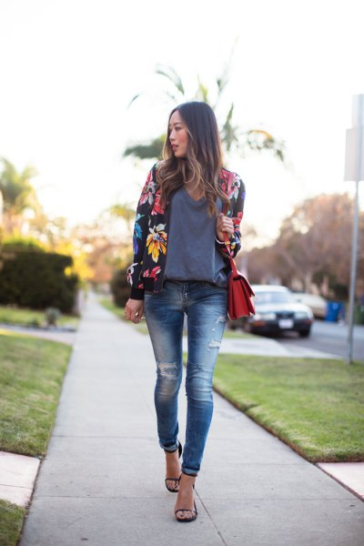 black floral bomber jacket with grey sweater and ripped skinny jeans
