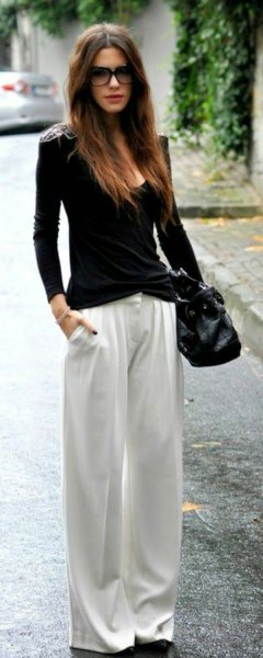 black form fitting scoop neck sweater with white pants