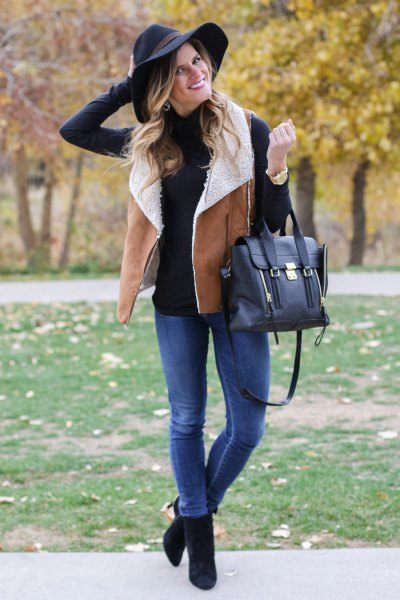 black mock neck sweater with camel shearling vest and blue jeans