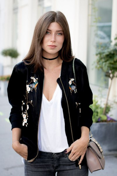 bomber jacket with low cut white vest top and black choker