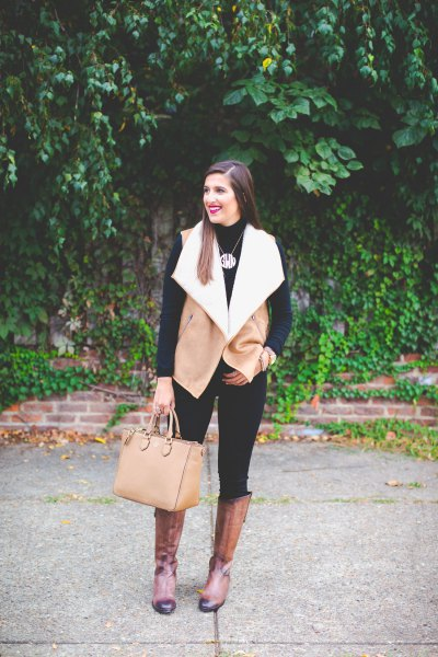 camel and white shearling vest with black skinny jeans and knee high boots