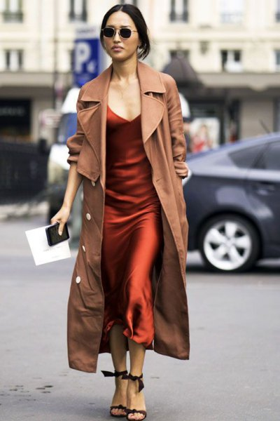 camel maxi trench coat over burgundy silk maxi slip dress