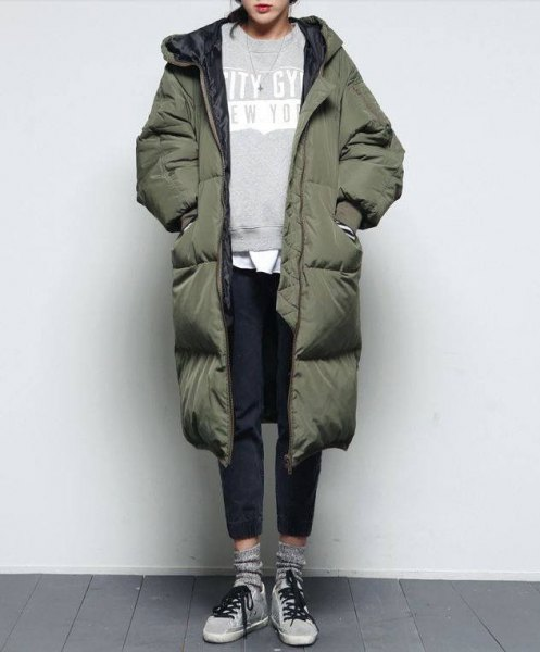 green long puffer coat with grey sweatshirt and black jeans