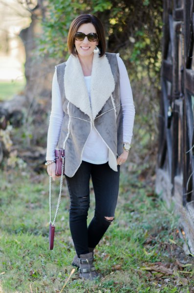 grey vest with black ripped jeans and suede ankle boots