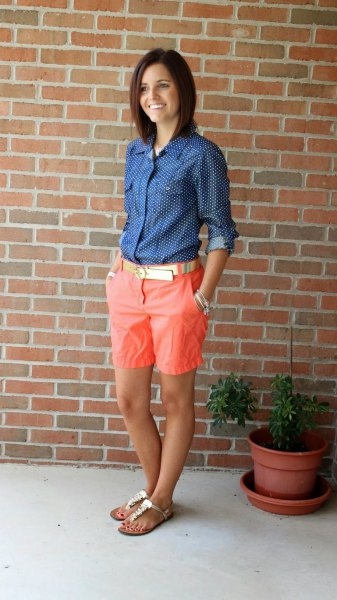 navy and white polka dot button up shirt with longer orange shorts