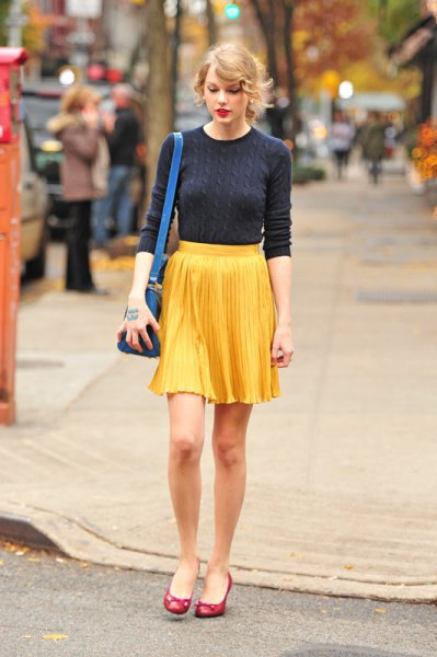 navy cable knit form fitting sweater with yellow pleated mini skirt