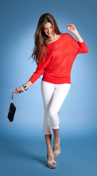 orange long sleeve top with white skinny crop jeans