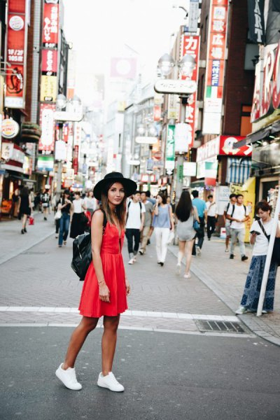 red mini sundress with white sneakers and black felt hat
