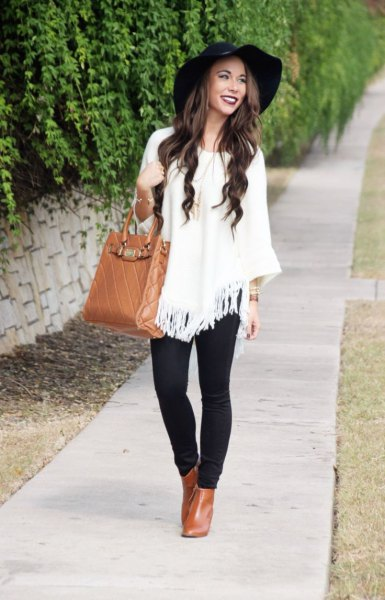 white fringe poncho sweater with black floppy hat