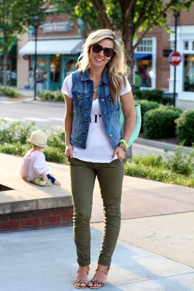 white print tee with denim vest and green skinny jeans