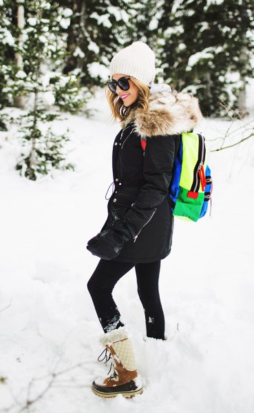 black coat with leggings and white and brown mid calf snow boots