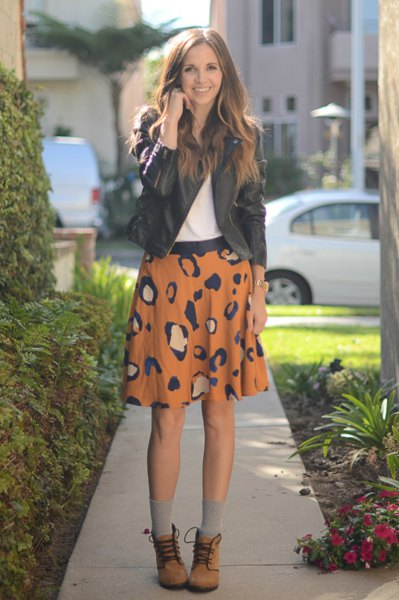 black leather jacket with orange printed mini skirt and lace up ankle boots