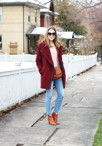 burgundy coat with ivory knit sweater and light blue skinny ankle jeans