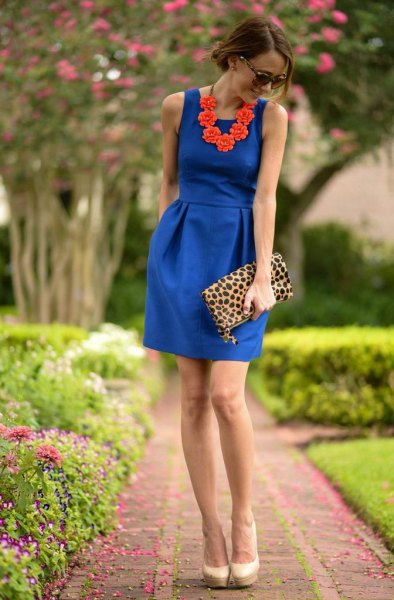 cobalt blue sleeveless gathered waist mini dress with leopard print clutch bag