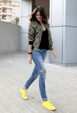 floral printed bomber jacket with black deep v neck vest top and yellow sneakesr