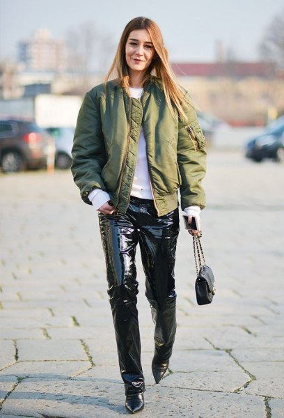 green satin bomber jacket with white sweater and black leather pants