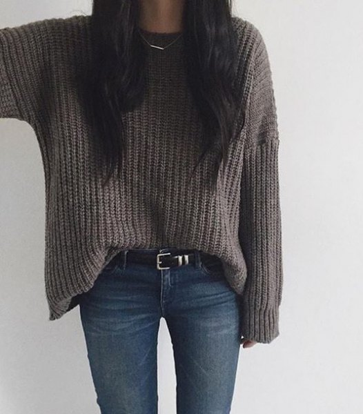 grey chunky knit sweater with dark blue skinny jeans and belt