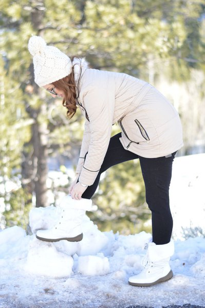 ivory zip front jacket with black leggings and white snow boots