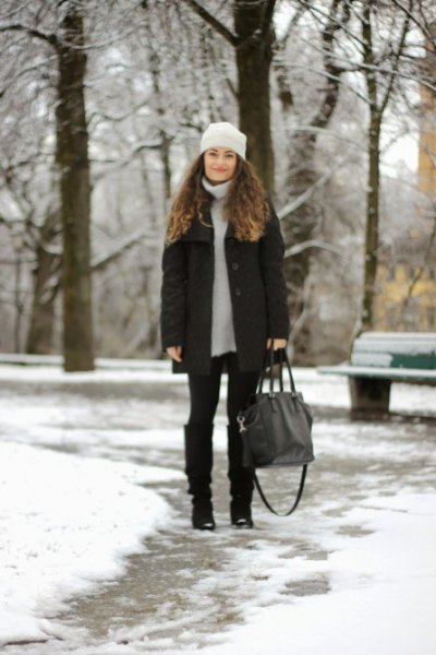 light grey sweater dress with down jacket and black knee high snow boots