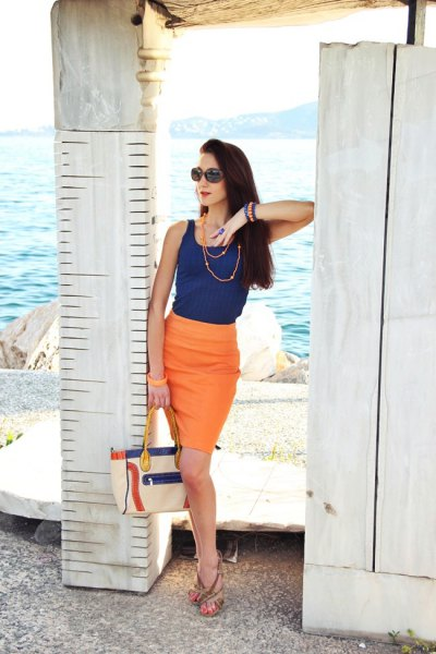 navy vest top with orange bodycon knee length skirt