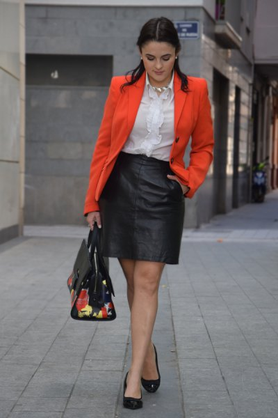 orange blazer jacket with white ruffle blouse and black mini leather skirt