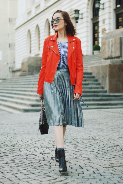 orange leather jacket with checkered blouse and silver pleated skirt