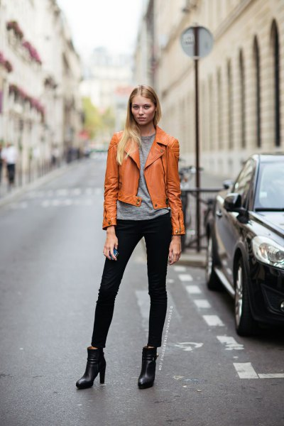 orangey brown leather jacket with grey tee and black jeans