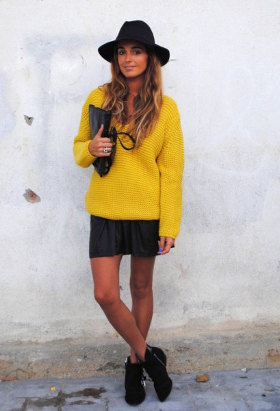 yellow chunky sweater with mini skirt and black felt hat