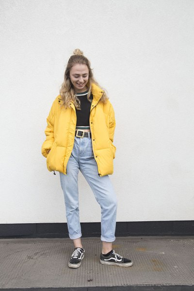 yellow puffer jacket with black cropped sweater and mom jeans