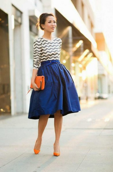 black and white patterned top with royal blue flared skirt and orange heels