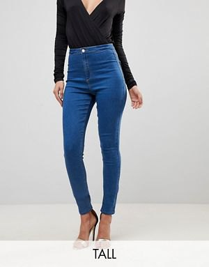 black deep v neck form fitting long sleeve top with blue tall jeans