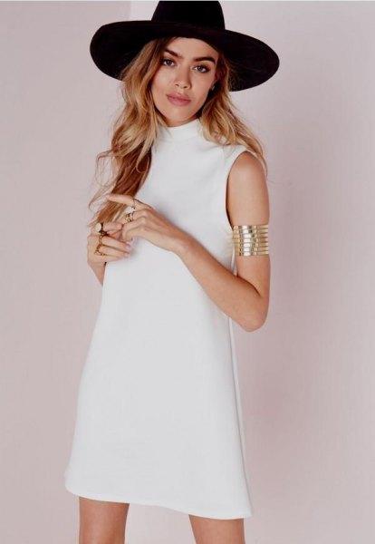 black felt hat with white sleeveless mock neck shift dress