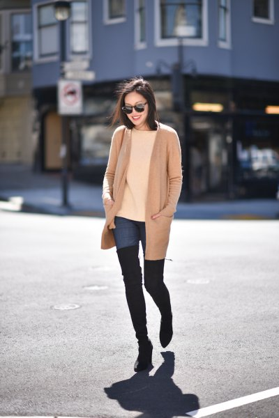 blush pink long jacket with blue tall jeans and black thigh high boots