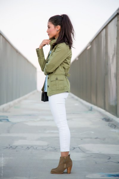 blush pink military jacket with white ankle skinny jeans and camel boots