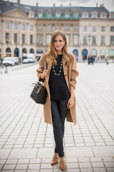 camel longline jacket with black sweater and leather pants