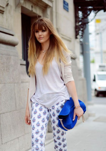 grey scoop neck sweater with white printed pants and royal blue suede purse