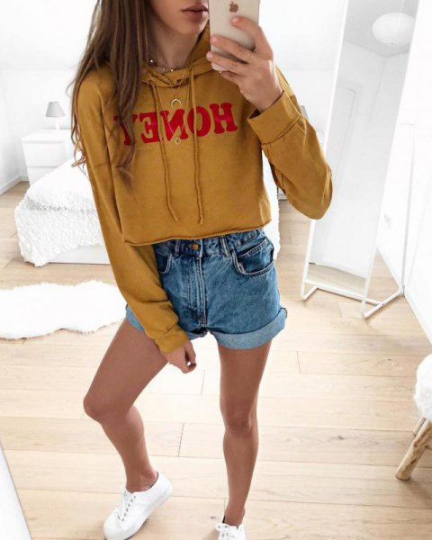 mustard yellow printed cropped hoodie with blue mini denim shorts