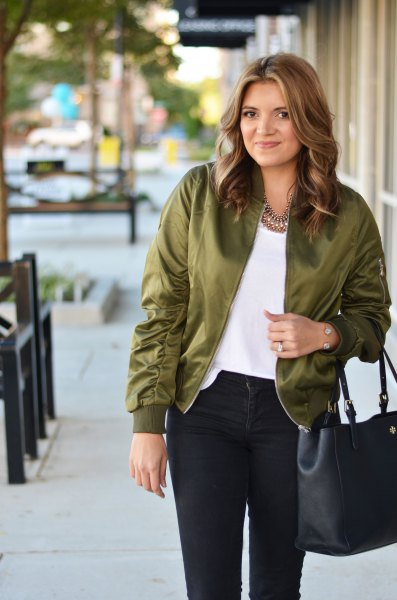 olive bomber jacket with white tee and black jeans