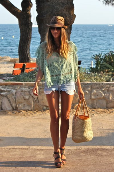 pale pink crochet top with mini denim shorts and beach straw bag