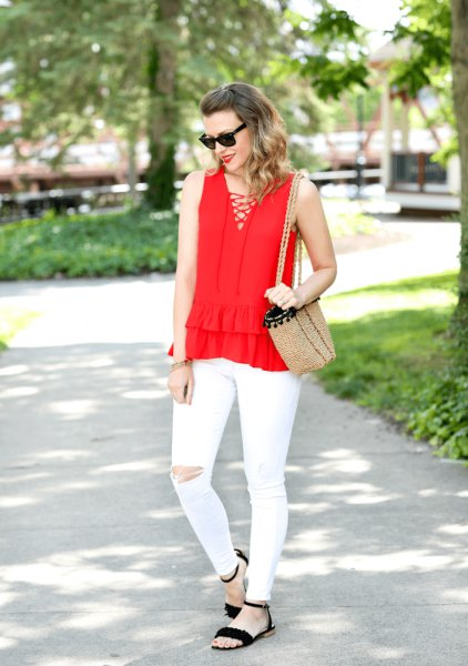 red criss cross front v neck sleeveless blouse with white ripped jeans