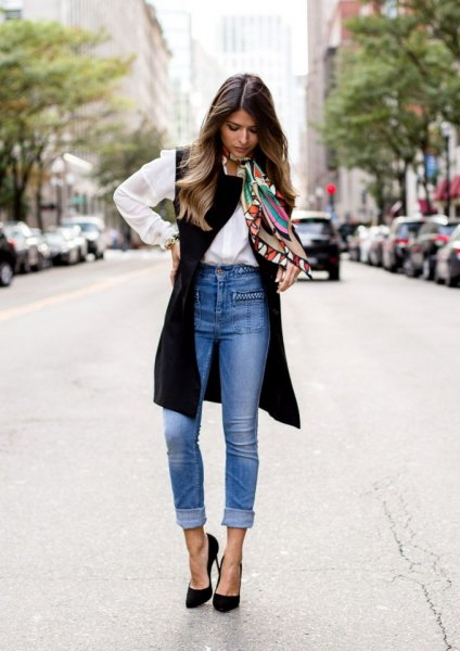 white button up shirt with black long vest and blue cuffed high waisted jeans